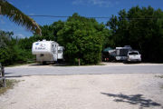 Photo: Buttonwood: Paved road with two campsites and campers on each site in background.