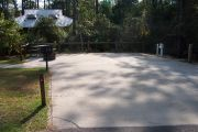 Shady RV/Trailer site with concrete pad for ADA accessibility.