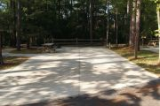 ADA-accessible campsite with concrete pad, picnic table and concrete sidewalk.