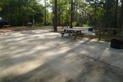 View of ADA-accessible campsite with accessible ground grill, picnic table and concrete pad.