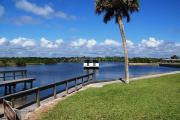 A boat launch and basin located on the Intracoastal Waterway. There is green grass, a palm tree and blue skies with beautiful cumulus clouds. A catwalk runs along both sides of the boat launch.