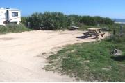 Packed sand campsite with low palmetto plants and sea oats along the back.  The ocean is visible. Low vegetation borders the left side. Picnic table is on the right of the site and ground grill is located at the back of site.