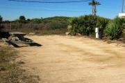 Packed sand campsite with palmetto plants along the right side. Picnic table and ground grill off to the left of the campsite. Electric and water hookups located to the right of the campsite. Large palmetto plants provide privacy from adjacent site.