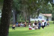 View shows people of various ethnic backgrounds picnicking on a grassy slope. There are people grilling and eating at picnic tables. The lawn is partially shaded by tree cover, and the Recreation Hall facility can be seen in the background.