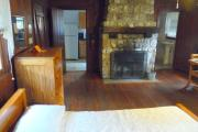 View inside an historic cabin. There is one room with a bed, dresser, table, and fire place. The floors and walls are wood and the fire place is made of stone. Just beyond the fireplace are the kitchen to the left and the bathroom to the right. These rooms are tiled and the walls are white.