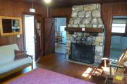 View inside an historic cabin. There is one room with a bed, dresser, futon, and fire place. The floors and walls are wood and the fire place is made of stone. Just beyond the fireplace are the kitchen to the left and the bathroom to the right. These rooms are tiled and the walls are white.