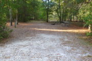 View of a vacant campsite with a picnic table, fire ring, and electric pedestal. The main part of the site is sandy. There are trees on all edges and two large trees at the back of the site. The site is partially shaded.