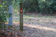 Close up of a brown site marker on a wooden post. An electric pedestal is located to the left of the post and there are dense bushes in the background.