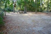 View of a vacant campsite with a picnic table, fire ring, and electric pedestal. The main part of the site is sandy with some small patches of grass. Several medium size trees are located at the back of the site. There is partial shade.