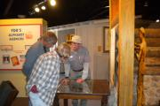 A friendly volunteer is explaining park history through an exhibit to a casually dressed man and woman in a museum.
