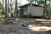 Cabin with picnic table and ground grill.