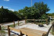 Photo: 002, View from shore over campsite fence rails with campfire ring and picnic table on the right side.  Campground road is visible on far side of campsite. Green vegetation surrounds portions of the site.