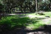 This is a picture of campsite 12 from the back of the site looking toward the road.   The site has water and 50amp electric service.  This is a partly sunny site with a gravel foundation.  The site has a picnic table and a ground campfire ring.
