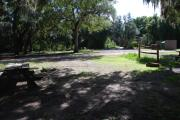 This is a picture of campsite 18 from the back of the site looking toward the road.   The site has water and 50amp electric service.  This is a partly sunny site with a gravel foundation.  The site has a picnic table and a ground campfire ring.