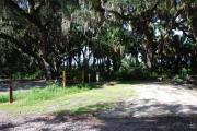 This is a picture of campsite 18 looking from the road into the partly sunny site.  This site has 50amp service and water hookups.  There is a gravel foundation with a picnic table and a ground campfire ring.