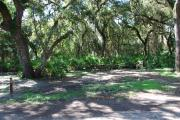 Campsite 26 is a shady tent only site with a gravel foundation located on the right hand side of the road.  Looking into the site on the right is the water and 50amp electrical service. There is a picnic table and ground campfire ring.  At the front left side of the site is the brown site marker.