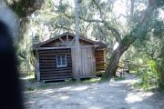 This is a front view picture of Cabin 1 which is a rustic palm log cabin built by the Civilian Conservation Corp. in the mid 1930's.  This cabin is ADA accessible.  There is a living/dining/bedroom area with 2 double beds, a sofa bed, dining set, linen cabinet and fireplace.  There also is a bathroom and a kitchen with coffee maker, toaster, microwave, range, refrigerator, dishes, silverware and cooking utensils.  The cabins sleep up to six. Off of the back porch, there is a fire ring, cooking grill and a picnic table.  There are no pets and no smoking allowed in the cabins.