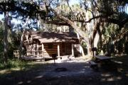 This is a back porch view picture of Cabin 1 which is a rustic palm log cabin built by the Civilian Conservation Corp. in the mid 1930's.  This cabin is ADA accessible.  There is a living/dining/bedroom area with 2 double beds, a sofa bed, dining set, linen cabinet and fireplace.  There also is a bathroom and a kitchen with coffee maker, toaster, microwave, range, refrigerator, dishes, silverware and cooking utensils.  The cabins sleep up to six. Off of the back porch, there is a fire ring, cooking grill and a picnic table.  There are no pets and no smoking allowed in the cabins.