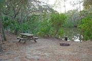 View of picnic table and grill on creek bank