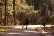 A bicyclist and rollerblader enjoy the Gainesville-Hawthorne trail.  This 16 mile long, paved Rails-to-Trails trail is popular with bicyclists, pedestrians, and equestrians.""