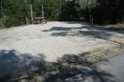 A view of the campsite with a shell/sand base and native vegetation.