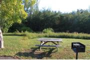Photo: 012, PRIM. Cabin #12 at Oleta River has a barbeque grill and a picnic table.