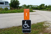 Photo: 001, View of site number post white on brown with ADA accessible sign, Bushes and camper trailers visible in the back ground.
