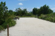 Photo: 028, View of gravel campsite with picnic table and grill. Bushes and trees in background.