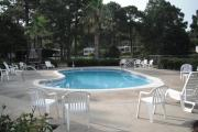 A view of the campground pool at Topsail Hill State Park with chairs for relaxing and RV campers visible in the background.
