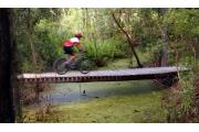 Off-road bike rider speeding across wooden bridge spanning vegetation infested creek.
