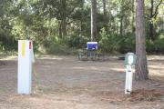 Photo: 9, Campground. In the site is a ground fire ring and a picnic table; electric and water hookups can be seen.